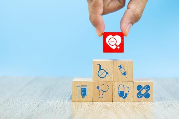 Opieka zdrowotna i medyczne symbole na drewnianych blokach dla pojęć ubezpieczenia zdrowotnego.