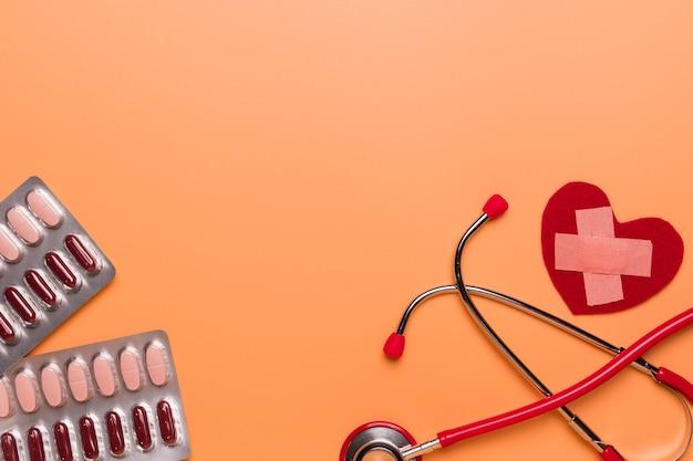 Opieka zdrowotna i medycznego pojęcia czerwony stetoskop i medycyna na pomarańczowym tle