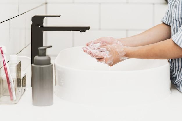 Opieka zdrowotna koncepcji pandemii covid19 zbliżenie azjatyckie mycie rąk wodą z kranu