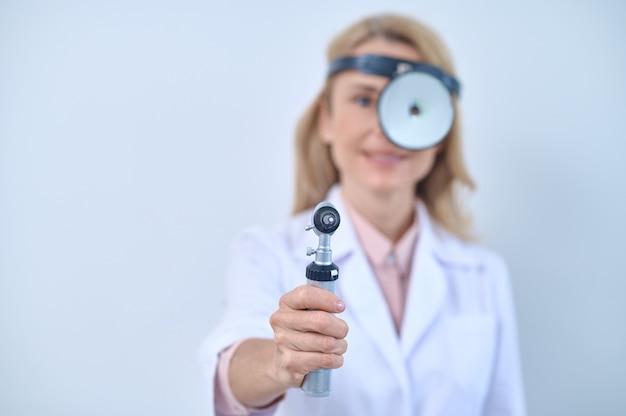 Opieka zdrowotna. przyjazna dorosła kobieta w białym fartuchu z lustrem i otoskopem w wyciągniętej dłoni stojącej na jasnym tle