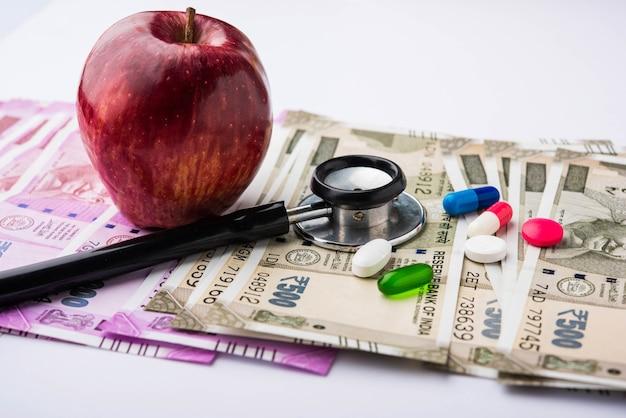 Opieka zdrowotna w indiach - koncepcja zdrowia i biznesu przedstawiająca indyjskie papierowe banknoty, stetoskop, pigułki, kalkulator, owoce jabłkowe i nadziewaną zabawkę w kształcie serca. selektywne skupienie