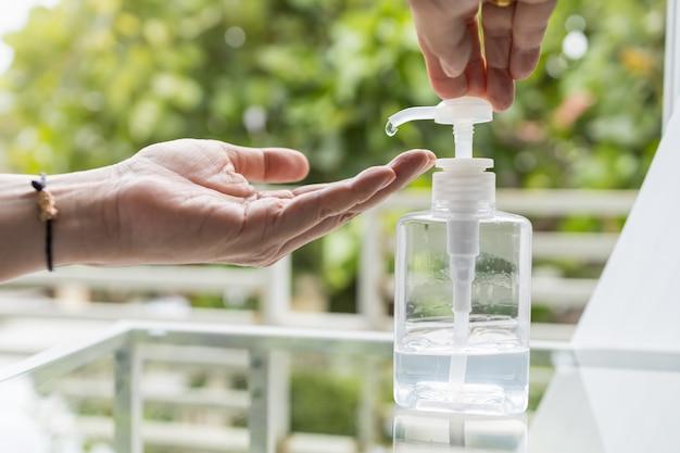 Opieka zdrowotna, wirus, koronawirus, covid-19, 2019-ncov koncepcja ochrony. zamyka up mężczyzna ręki pchnięcie i używać alkoholu gel sanitizer na ręce.