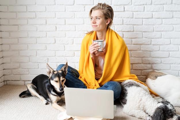 Opieki nad zwierzętami. zabawna młoda kobieta w żółtej kratę siedzi na podłodze z psami pijąc kawę