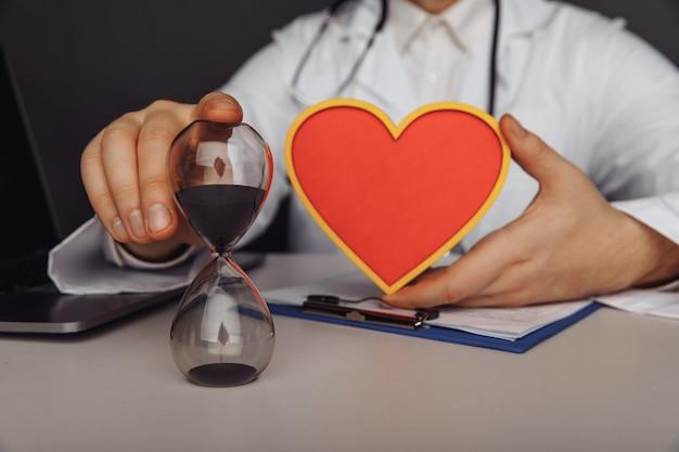Opieki zdrowotnej i medycznej koncepcja mężczyzna lekarz z drewnianym sercem i klepsydrą