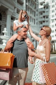Opiekować się. uśmiechnięta piękna kobieta przestawia okulary swojej córki siedzącej na ramionach ojca po zakupach.