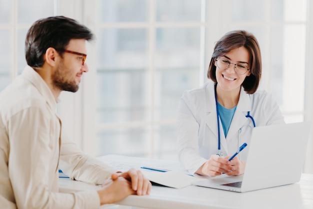 Opiekująca się lekarka wydaje recepty pacjentowi, siedzi razem przy stole i patrzy na komputer