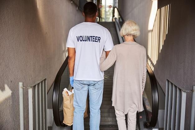 Opiekun i emeryt stojący przed ruchomymi schodami plecami do kamery to