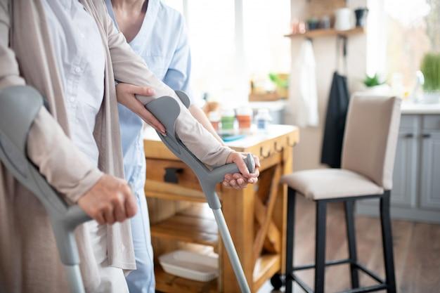 Opiekun medyczny pomaga emerytowi chodzić po mieszkaniu