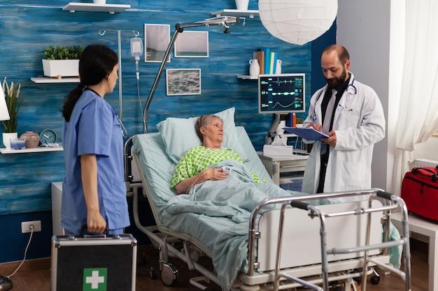 Opiekun pielęgniarka mężczyzna pisze leczenie leków w schowku