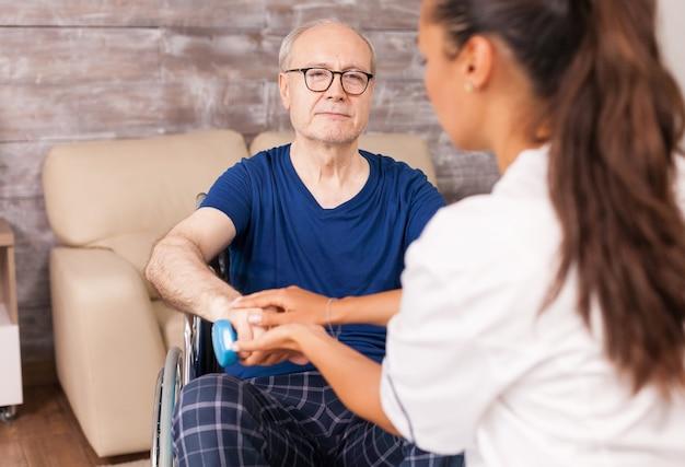 Opiekun pomagający sparaliżowanemu mężczyźnie w powrocie do zdrowia za pomocą hantli na mięśnie ramion