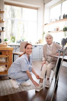 Opiekun uśmiecha się, pomagając starszej kobiecie zasznurować buty
