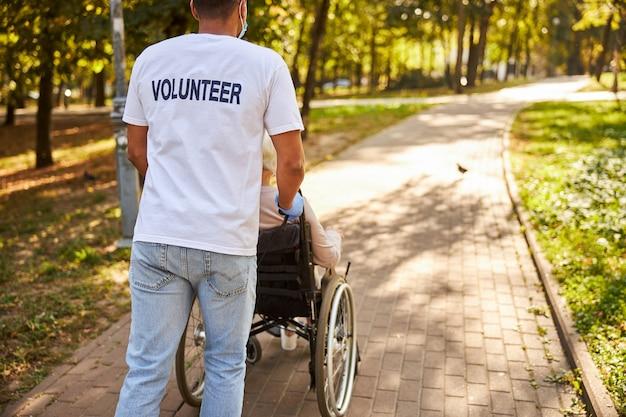Opiekun w białej koszulce i dżinsach pchający wózek inwalidzki ze starszą kobietą przez jasną aleję parkową