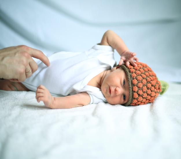 Opiekuńcza ręka matki pieszczącej noworodka