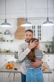 Opiekuńczy zamyślony ojciec mocno przytulający córkę w kuchni.