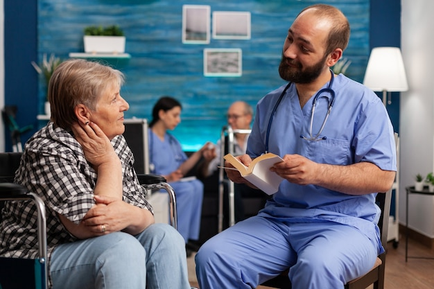 Opiekunowie wspierają pielęgniarkę czytającą historie książkowe seniorowi niepełnosprawnemu renciście
