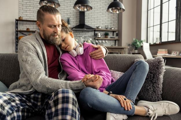 Opierając się na ramieniu. nastoletnia córka ubrana w dżinsy i trampki opierając się na ramieniu wspierającego ojca