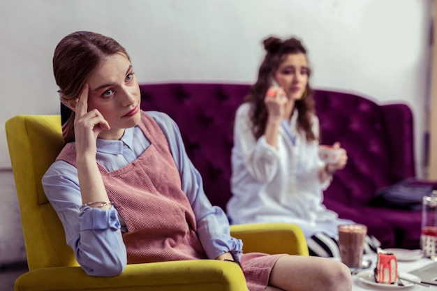 Opisywanie sytuacji. sceptyczna nieszczęśliwa dziewczyna w różowej sukience niezadowolona z braku uwagi ze strony przyjaciółki