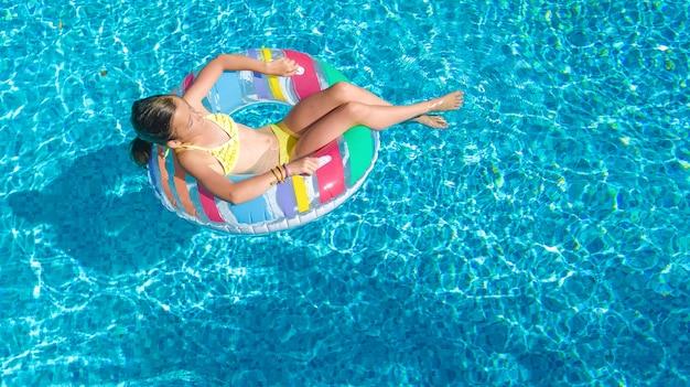 Opisz dziewczynę w basenie z lotu ptaka z góry, dziecko pływa na dmuchanym pierścieniu, dziecko bawi się w niebieskiej wodzie w rodzinnym kurorcie