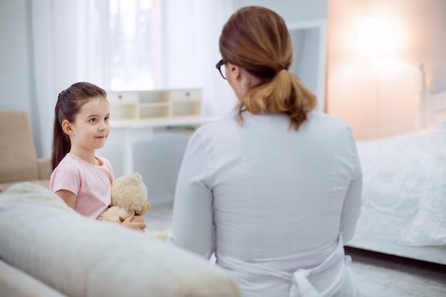 Opisz swój stan. urocza dziewczyna pewnie patrząc na lekarkę siedzącą na kanapie i rozmawiając z nią