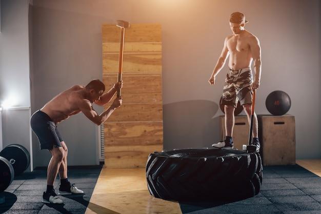 Opona młotkowa uderza mężczyzn po treningu na siłowni z oponą młotka i ciągnika