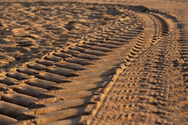 Opona samochodowa drukuje na piasku podczas dnia, selekcyjna ostrość.