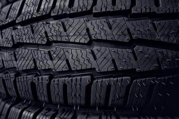 Opony z bliska. czarny profil opony zimowej z kolcami. opony samochodowe z rzędu.