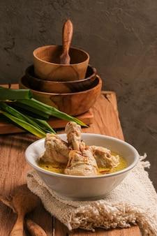 Opor ayam serwowany jest na drewnianym stole. opor to tradycyjna indonezyjska potrawa z kurczaka gotowana z sosem z mleka kokosowego