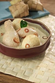 Opor ayam telur, kurczak i gotowane jajko gotowane w indonezyjskim mleku kokosowym, podawane z lontongiem lub ketupatem i sambalem. popularne danie dla lebaran lub id al-fitr