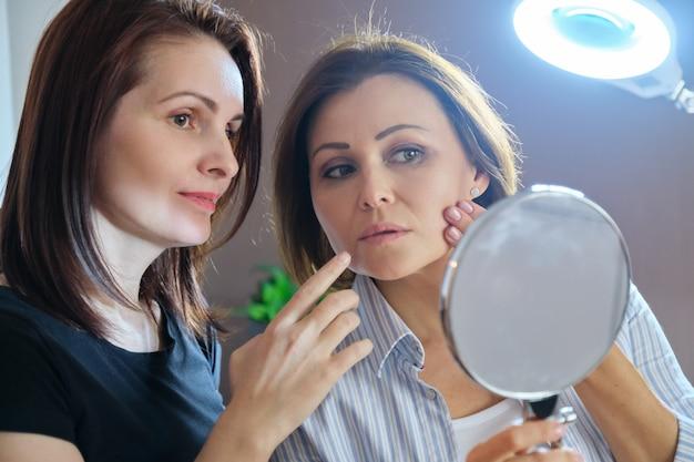 Opowiadające i uśmiechnięte kobiety kosmetyczka i dojrzała pacjentka z lustrem w salonie piękności