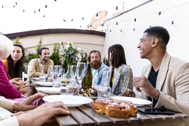 Opowiadający historię wieloetnicznej grupy ludzi jedzących posiłki na dachu. rodzina i przyjaciele spotykają się w domu