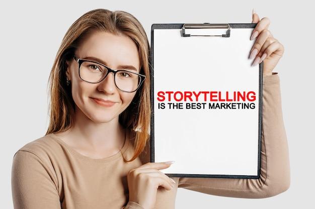 Opowiadanie historii to najlepszy marketing. piękna młoda biznesowa kobieta w okularach trzyma schowek z makietą miejsca na szarym tle