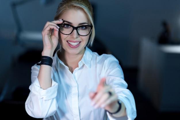 Opracowanie nowego języka programowania. uśmiechnięta młoda profesjonalna kobieta it siedzi w biurze i podczas pracy nad projektem korzysta z nowoczesnych technologii