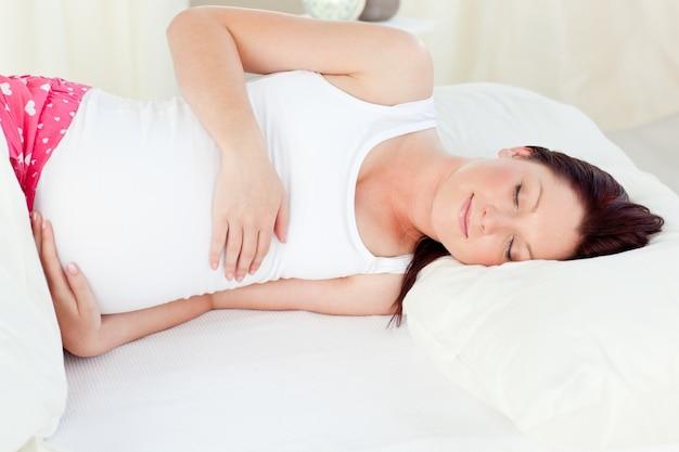 Opromieniony kobieta w ciąży dosypianie w jej łóżku