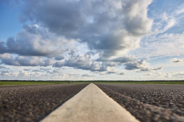 Opróżnia asfaltową drogę piękny chmurny niebo dalej, zakończenie