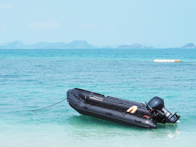 Opróżnia czarną nadmuchiwaną łódź w morzu