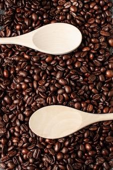 Opróżnia drewnianą łyżkę na kawowych fasoli tle. widok z góry.