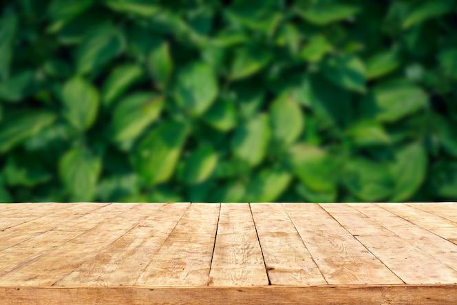Opróżnia drewnianego pokładu stół z ulistnienia bokeh tłem. gotowy do montażu wyświetlacza produktu.