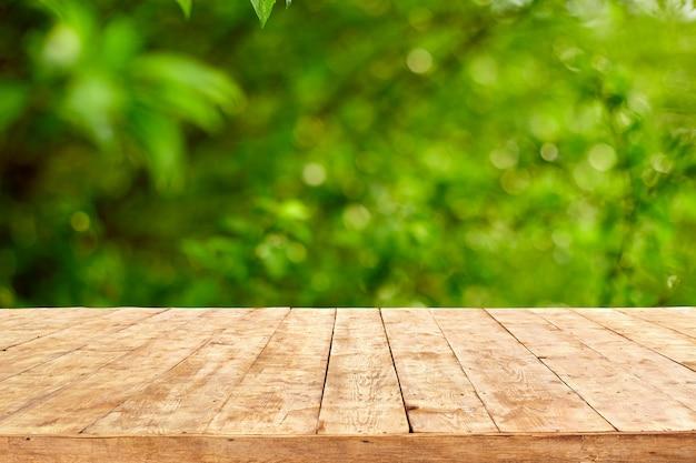 Opróżnia drewnianego pokładu stół z ulistnienia bokeh tłem.