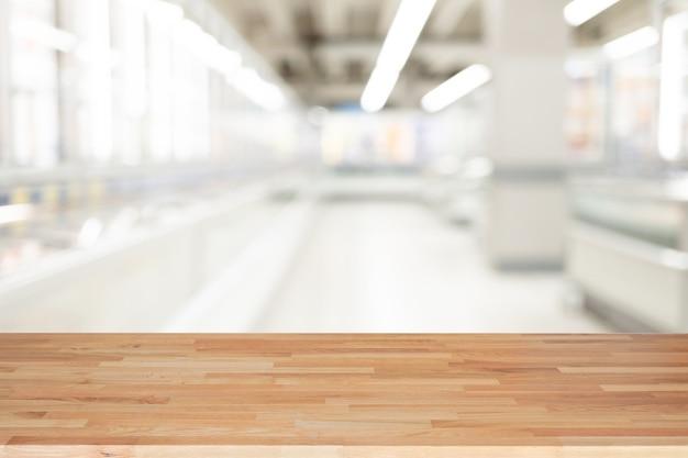 Opróżnia drewnianego stół i wewnętrznego tło, produktu pokaz, zamazany lekki wewnętrzny tło z bokeh wydziałowym sklepem, przygotowywający dla produktu montażu.