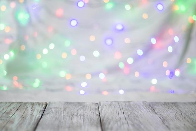 Opróżnia drewnianego stołu lub półki ścianę na kolorowym bokeh tle.
