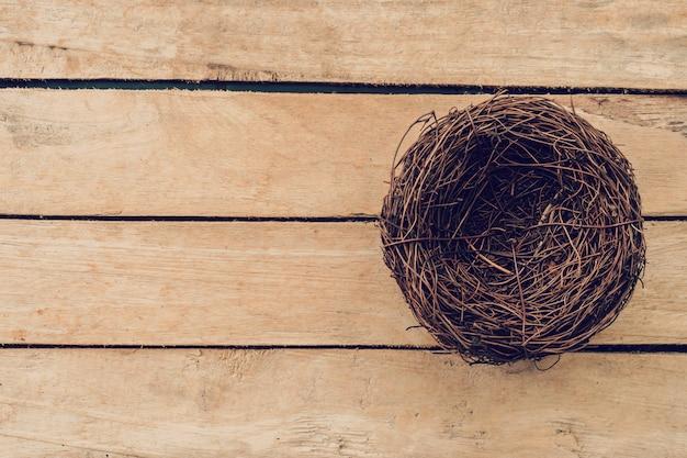 Opróżnia gniazdeczko na drewnianym stole i tle z kopii przestrzenią