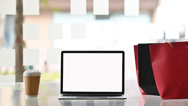 Opróżnia parawanowego laptop i torba na zakupy z kawą na stole, czarny piątku pojęcie.