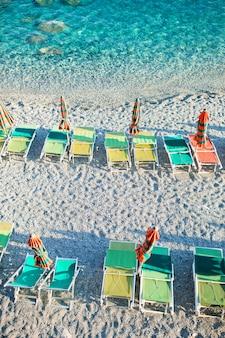 Opróżnia plażę z zamkniętymi parasolami na włocha wybrzeżu