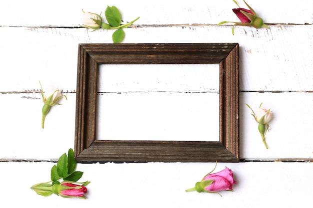 Opróżnia ramę dla fotografii pączków róży na białego drewnianego tła retro podławym modnym odgórnym widoku