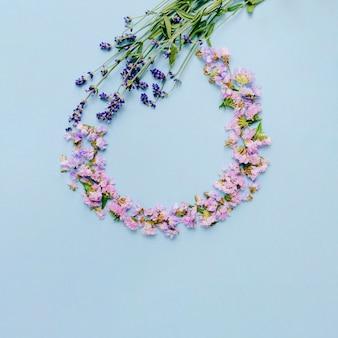 Opróżnia ramę robić z kwiatami na błękitnym tle