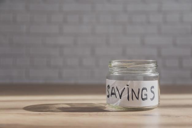 Opróżnia słój dla oszczędzać na stole z kopii przestrzenią w ścianie