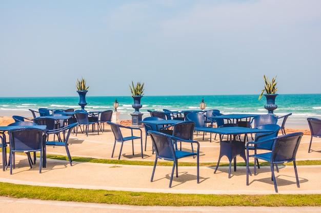Opróżnia stół i krzesła wokoło plażowego tła
