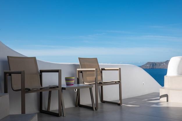 Opróżnia stół i krzesła z niebieskim niebem w santorini wyspie, grecja