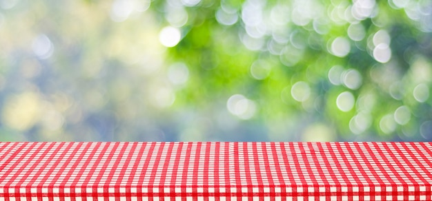 Opróżnia stół z czerwonym tablecloth nad plamy zielonym drzewem i bokeh tłem dla jedzenia i produktu pokazu montażu tła, sztandar