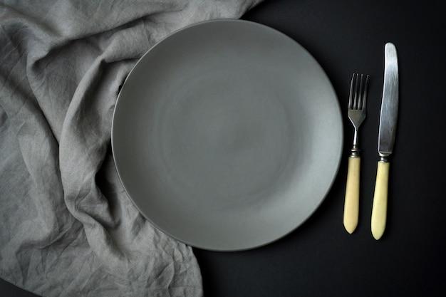 Opróżnia talerza na ciemnym tle. pusty szary talerz ceramiczny z nożem i widelcem do jedzenia i kolacji na ciemnym tle piękne.